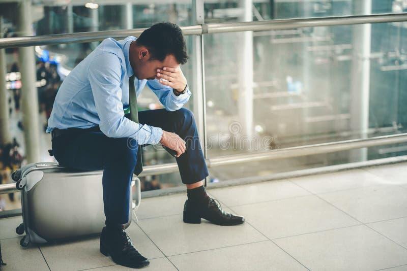 Um homem de negócios asiático está sentando-se em sua bagagem Foi forçado e olhou seu smartphone no aeroporto fotografia de stock
