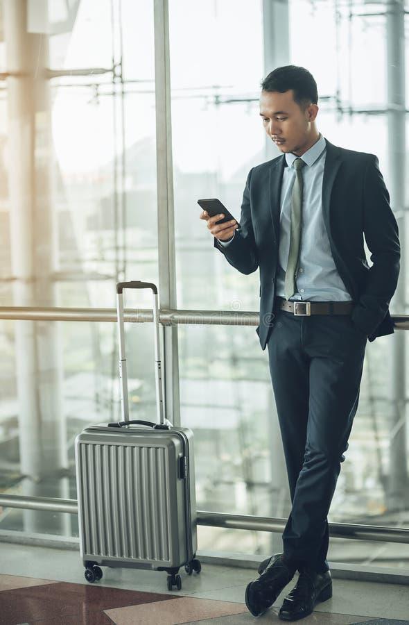 Um homem de negócios asiático está usando um smartphone para obter no wh do negócio imagens de stock royalty free