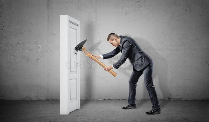 Um homem de negócios bate uma porta branca e fechado pequena mas suas rupturas do martelo imagem de stock