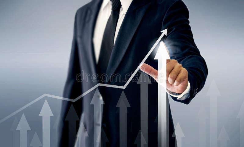 Um homem de negócios bem sucedido, mãos toca no gráfico que representa elevações do lucro sobre muito mais fotografia de stock royalty free