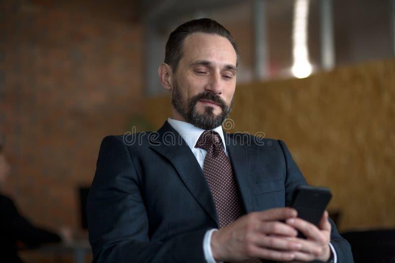 Um homem de negócios bem sucedido que lê uma mensagem de texto em um telefone celular ao sentar-se em seu escritório imagens de stock royalty free