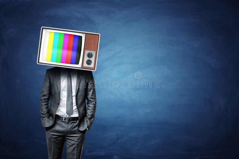 Um homem de negócios calmo com mãos em seus bolsos veste uma caixa velha da tevê com as barras de cor na tela imagens de stock