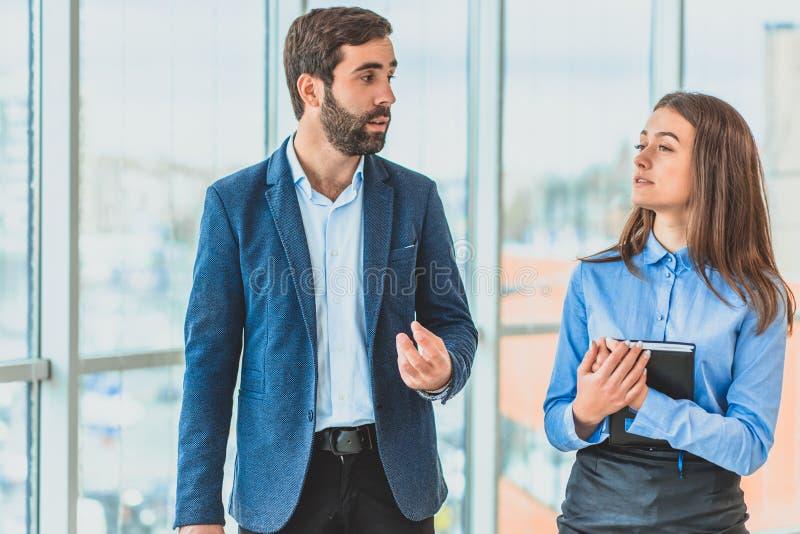 Um homem de negócios com seu secretário é vestido na roupa do negócio Durante isto falam imagens de stock royalty free