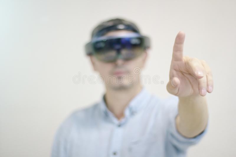 Um homem-homem de negócios com uns auriculares da realidade virtual controla sua mão Tecnologia futura imagem de stock