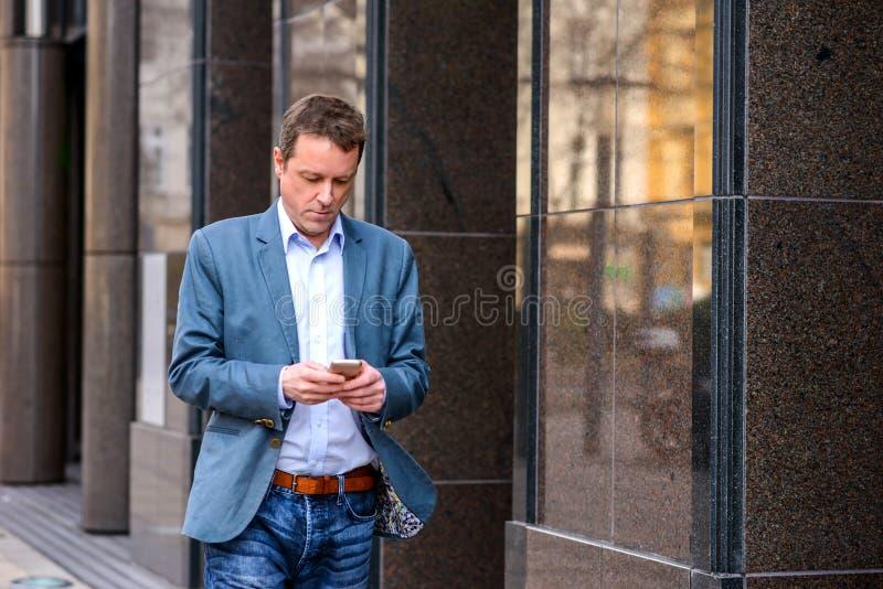 Um homem de negócios da Idade Média que anda com um telefone imagens de stock