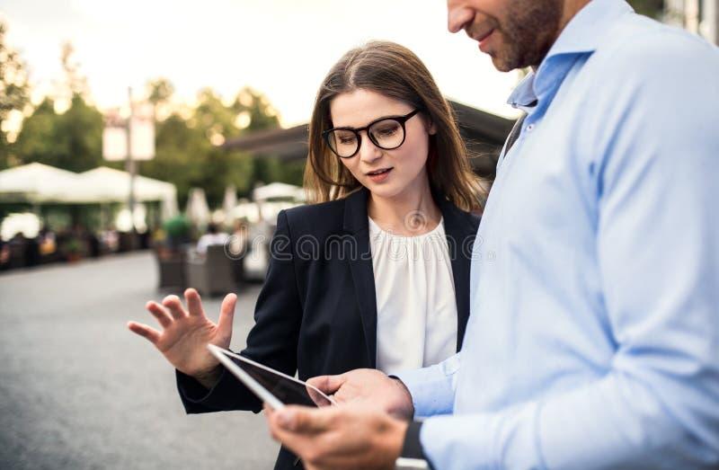 Um homem de negócios e uma mulher de negócios novos que usa a tabuleta fora fotos de stock royalty free