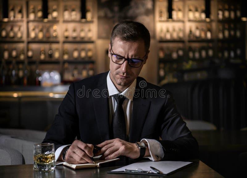 Um homem de negócios elegante, sério e concentrado que escreve as notas em seu caderno fotografia de stock royalty free
