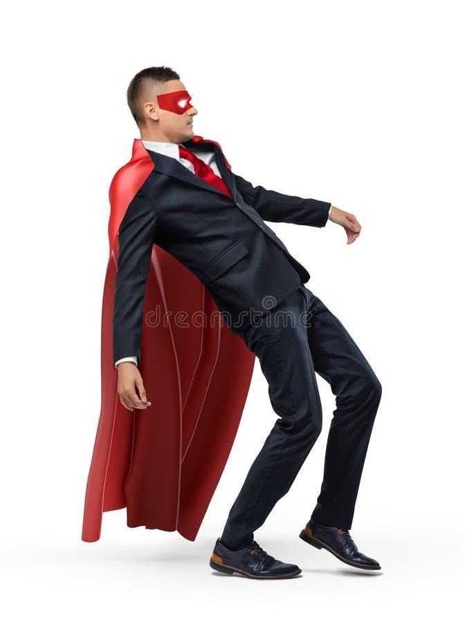 Um homem de negócios em um cabo vermelho do super-herói e em uma máscara que deslizam e que caem para trás fotos de stock royalty free