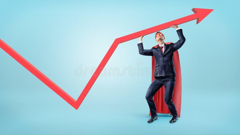 Um homem de negócios em um cabo vermelho do superman que apoia uma seta vermelha da estatística com suas mãos imagem de stock