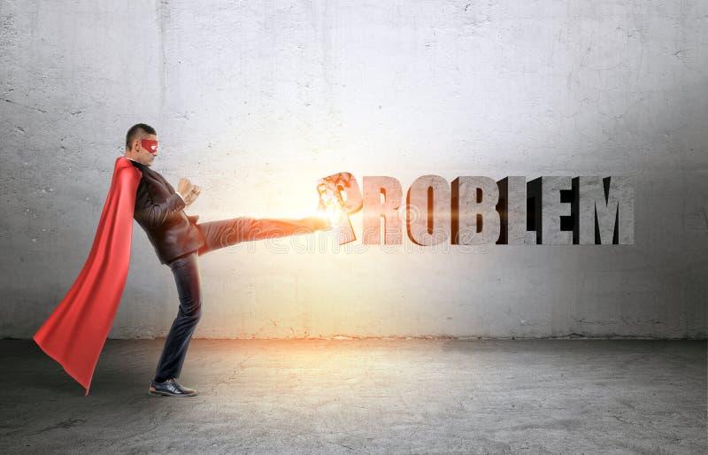 Um homem de negócios em um cabo vermelho e em uma máscara que batem uma escrita concreta do ` do problema do ` com seu pé imagens de stock