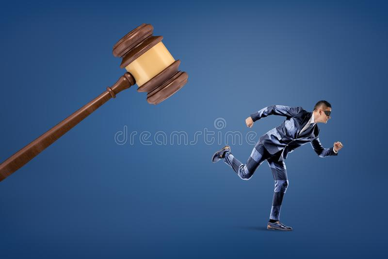 Um homem de negócios em uma máscara e em um terno listrado corre longe de um martelo de madeira gigante do juiz fotografia de stock royalty free