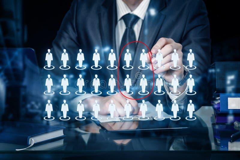 Um homem de negócios está circundando figuras humanas ícones entre o grupo inteiro na estrutura de gestão foto de stock