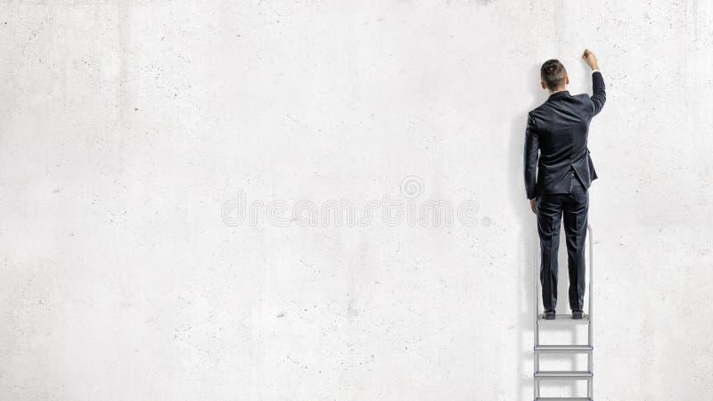 Um homem de negócios está em uma escada de etapa em uma vista traseira e tira em uma parede branca vazia imagens de stock royalty free