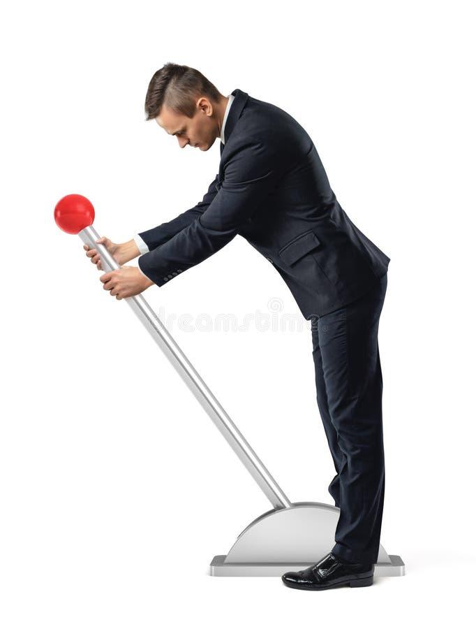 Um homem de negócios está em uma grande alavanca com um botão redondo vermelho e começa movê-lo foto de stock