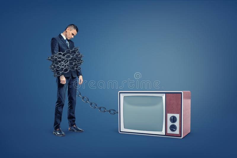 Um homem de negócios está encadernado por uma corrente enorme do ferro conectada a uma caixa retro da tevê imagens de stock royalty free