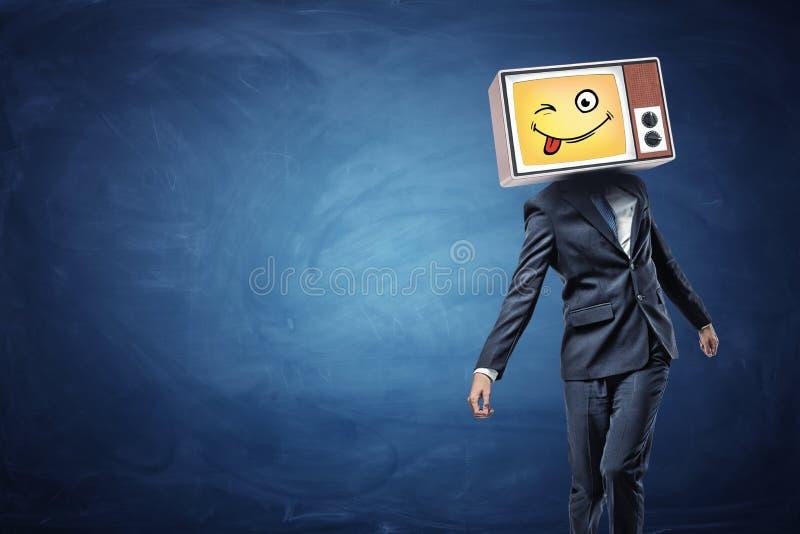 Um homem de negócios estranhamente de passeio veste uma tevê do vintage em sua cabeça e projeta um emoji amarelo com uma língua d foto de stock