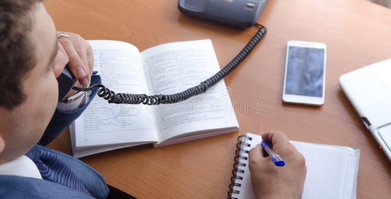 Um homem de negócios fala em um telefone da linha terrestre e faz anotações fotos de stock royalty free