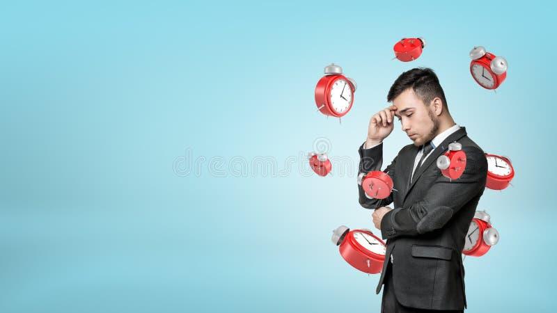 Um homem de negócios farpado novo profundamente no pensamento quando muitos despertadores retros vermelhos que voam em torno dele imagem de stock
