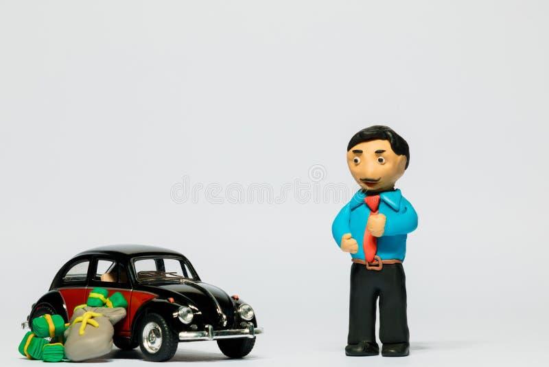 Um homem de negócios feito do plasticine ao lado de um carro e uma pilha de dinheiro no fundo branco fotos de stock