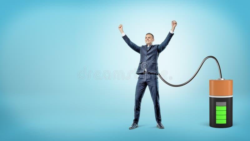 Um homem de negócios feliz com mãos levantadas é conectado a uma grande bateria que carrega o foto de stock