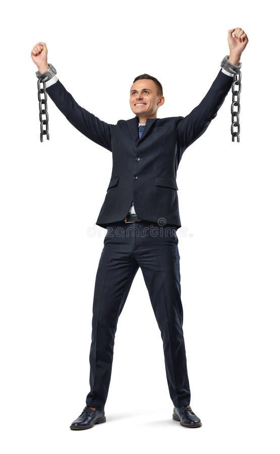 Um homem de negócios feliz com mãos levantou acima mostrar grilhões quebrados no fundo branco foto de stock royalty free