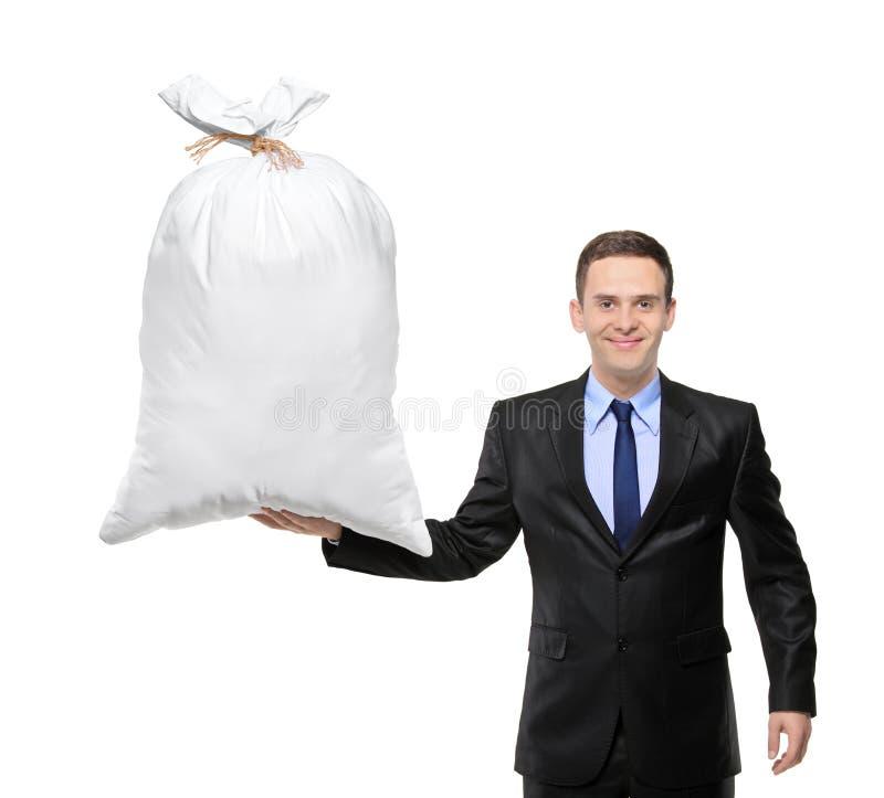 Um homem de negócios feliz que prende um saco com dinheiro imagem de stock