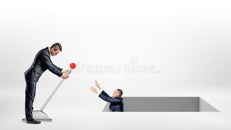 Um homem de negócios gerencie uma grande alavanca que ajuda um outro homem caído dentro de um grande furo quadrado na terra fotos de stock