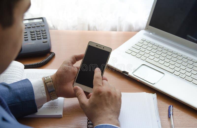 Um homem de negócios guarda um smartphone em suas mãos fotografia de stock royalty free
