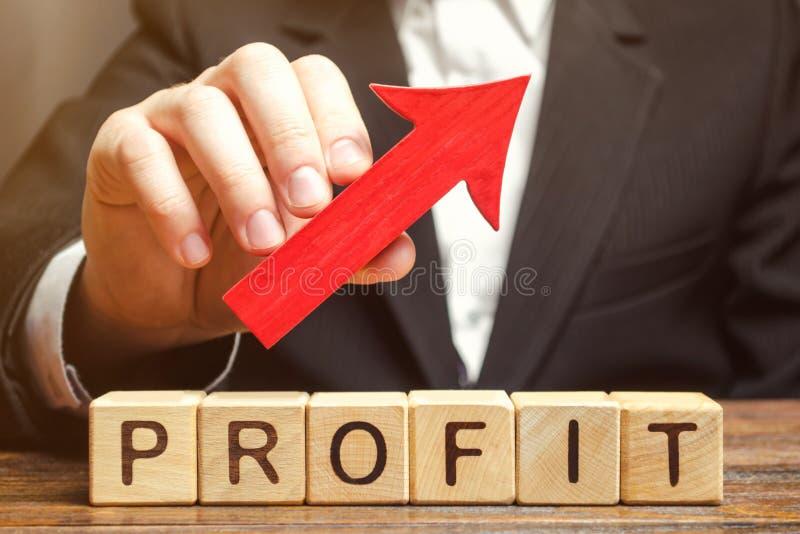 Um homem de negócios guarda uma seta vermelha acima sobre blocos de madeira com o lucro da palavra Negócio bem sucedido e lucros  foto de stock royalty free