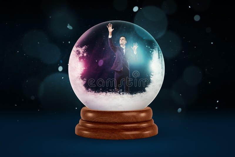 Um homem de negócios minúsculo dentro de uma bola de cristal nevado em um fundo escuro com as mancha da queda da neve imagens de stock royalty free