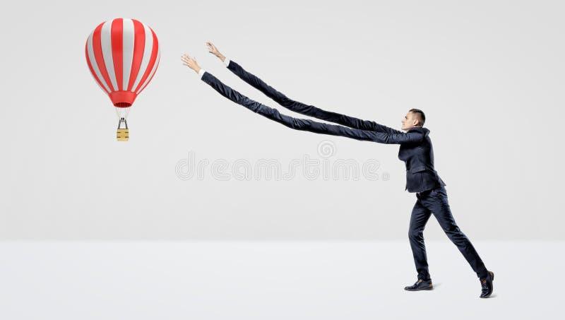 Um homem de negócios na vista lateral que tenta travar um grande balão de ar quente do voo com seus braços extra longos fotos de stock