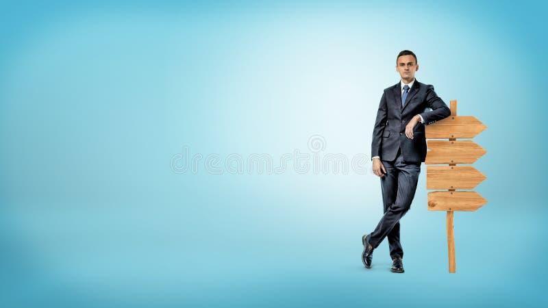 Um homem de negócios no fundo azul inclina-se ocasionalmente em um quadro indicador de madeira pequeno que mostra a maneira em so fotografia de stock royalty free