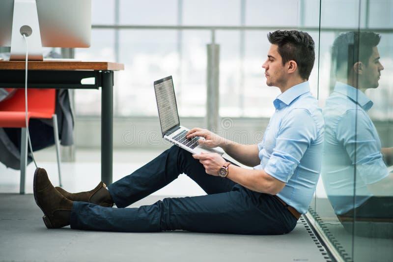 Um homem de negócios novo com o portátil que senta-se no assoalho no escritório, trabalhando imagens de stock royalty free