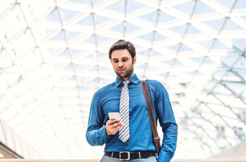 Um homem de negócios novo com smartphone que anda em uma construção moderna, texting foto de stock royalty free