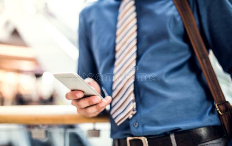 Um homem de negócios novo com smartphone que anda em uma construção moderna, texting fotos de stock royalty free