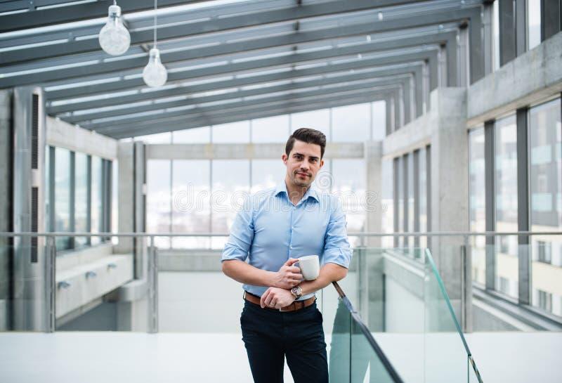 Um homem de negócios novo com a xícara de café no corredor fora do escritório fotos de stock