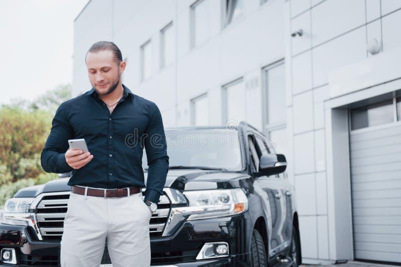 Um homem de negócios novo, contínuo e seu carro perto do escritório fotos de stock royalty free
