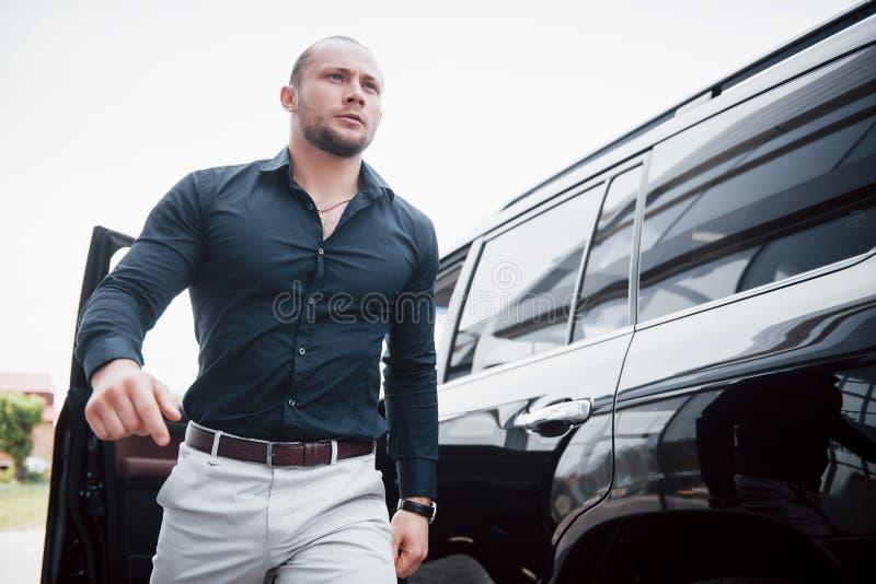 Um homem de negócios novo, contínuo e seu carro perto do escritório foto de stock royalty free