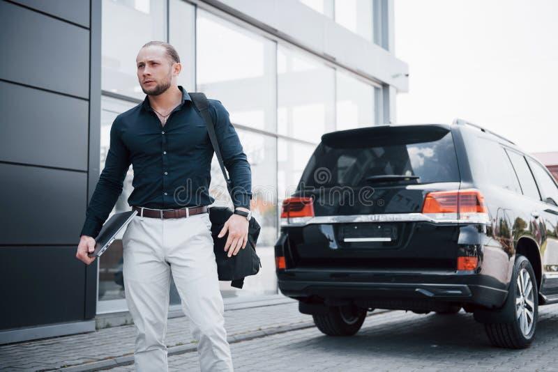 Um homem de negócios novo, contínuo e seu carro perto do escritório imagens de stock royalty free