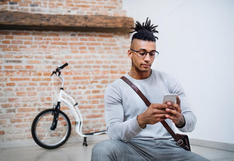 Um homem de negócios novo da raça misturada com o telefone no escritório fotografia de stock