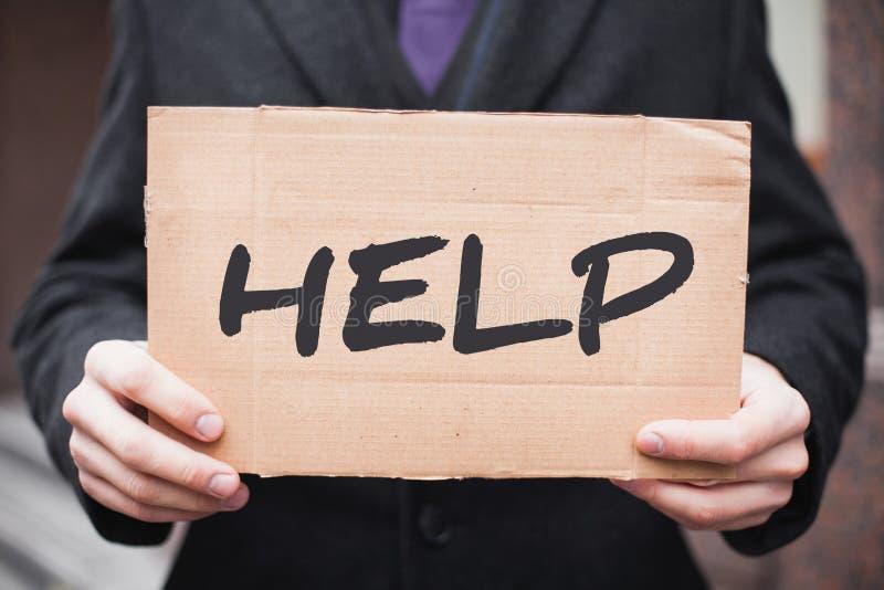 Um homem de negócios novo guarda uma tabuleta do cartão com a inscrição 'ajuda 'em suas mãos foto de stock