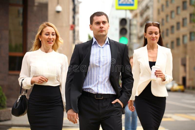 Um homem de negócios novo que anda na rua com seus secretários foto de stock royalty free