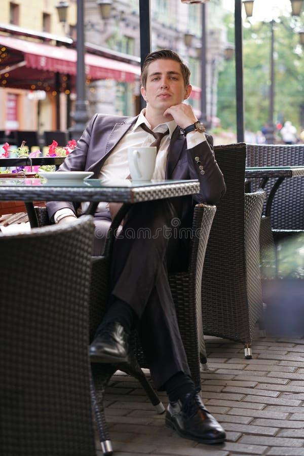 Um homem de negócios novo veio almoçar em um café, senta-se em uma tabela e espera-se alguém fotos de stock