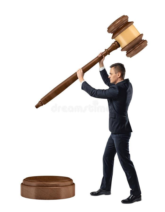 Um homem de negócios pequeno no fundo branco isolado guarda e abaixa um martelo gigante do juiz em um bloco sadio fotos de stock