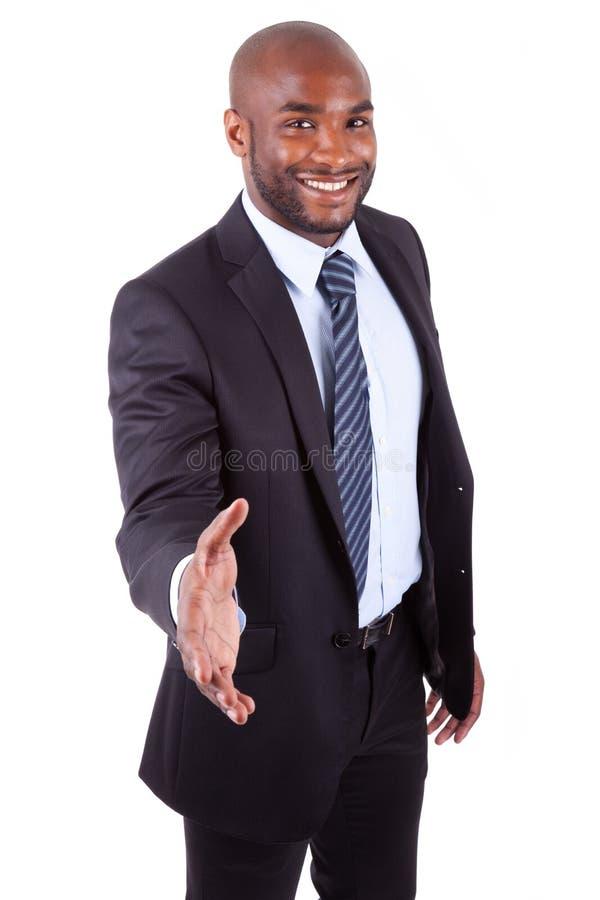 Um homem de negócios preto que dá uma mão imagem de stock