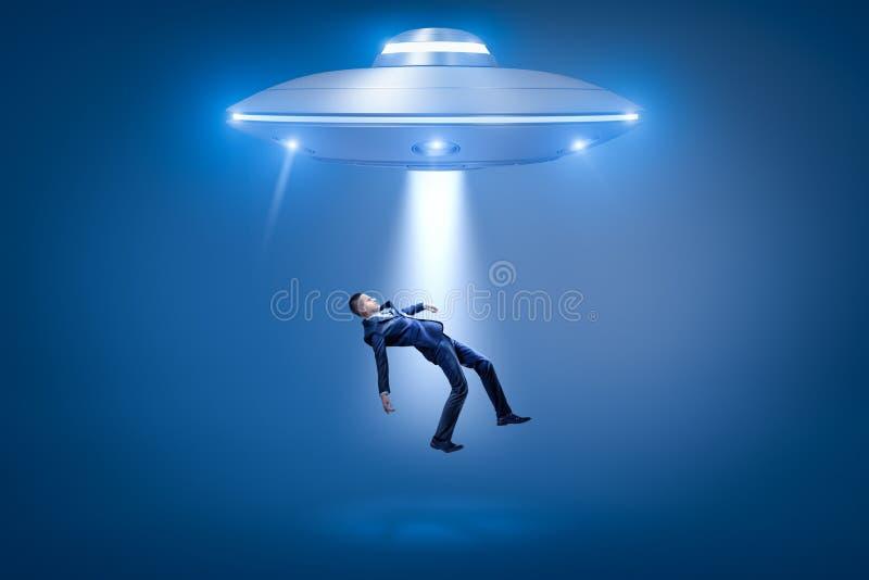 Um homem de negócios puxado para um portal aberto de um UFO por alguma força invisível fotos de stock
