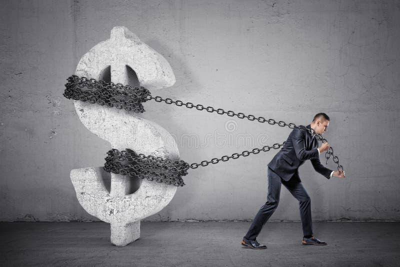 Um homem de negócios reboca em uma corrente que tenta mover um grande sinal de dólar concreto de seu lugar imagem de stock