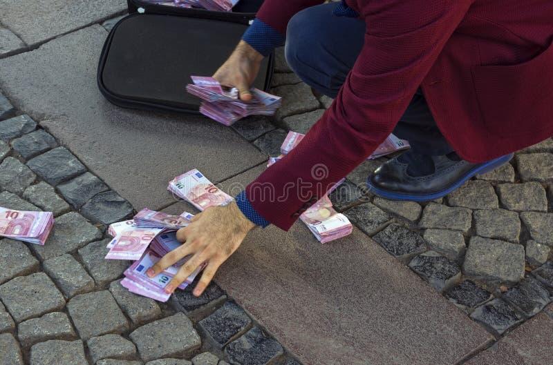 Um homem de negócios recolhe o dinheiro da terra fotos de stock royalty free