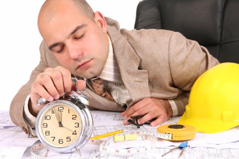 Um homem de negócios sonolento com plantas arquitectónicas imagem de stock royalty free