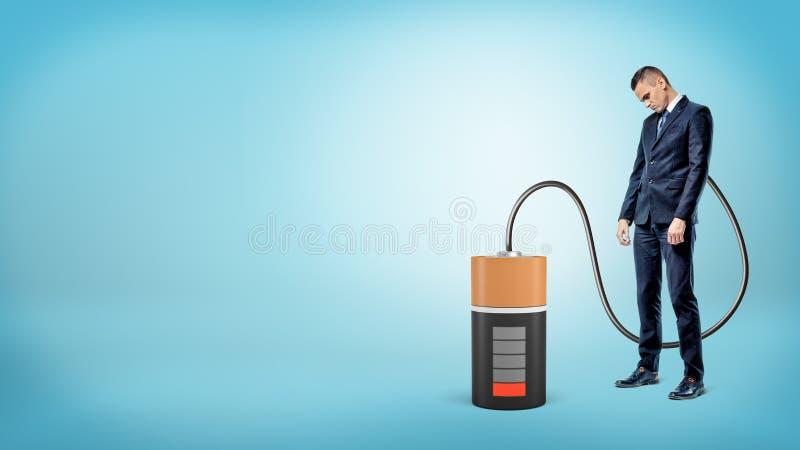 Um homem de negócios triste com sua cabeça está para baixo conectado pelo cabo a uma grande bateria vazia imagens de stock royalty free